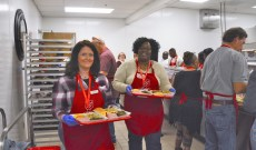 Volunteers Wendy Malone and Rikesha Foster head to the dining room with somebody's Thanksgiving dinner. (Karim Shamsi-Basha / Alabama NewsCenter)