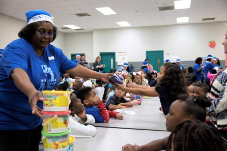 Project Blue Elf volunteers hand out toys to the kids at South Hampton K-8. (Brittany Faush / Alabama NewsCenter)