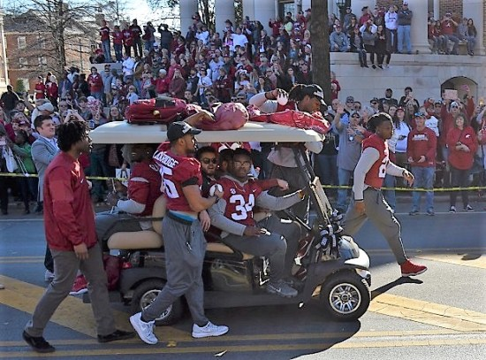 Alabama Crimson Tide running backs toss beads and footballs in the parade. (Michael Tomberlin / Alabama NewsCenter)