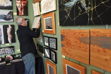 Artimaps' David Nuttall hangs a map in his Huntsville studio. (Karim Shamsi-Basha / Alabama NewsCenter)