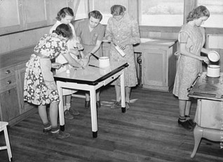 Cooking teacher and group of girls in home economics classroom at the Goodman School, Coffee County, 1939. (Photograph by Marion Post Wolcott, Library of Congress Prints and Photographs Division)