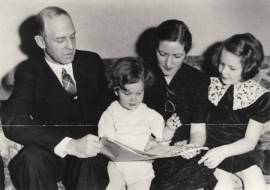 Senator Lister Hill looking at a newspaper with his wife, Henrietta, and their children, c. 1938. (Alabama Department of Archives and History)