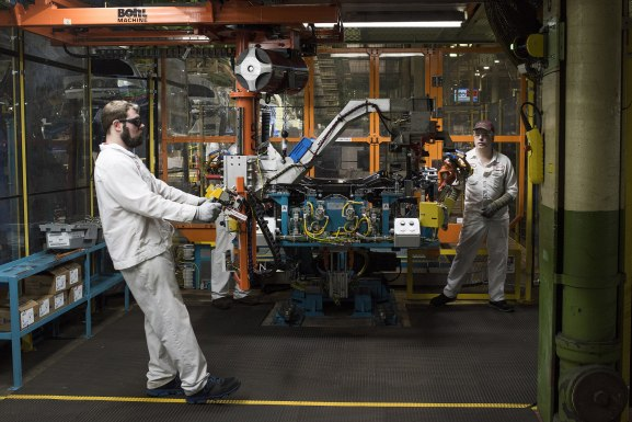 An employee moves a part into the rear suspension feeding the robotic assembly at Honda's Marysville, Ohio, plant. Honda still relies on humans for many auto assembly functions. (Ty Wright / Bloomberg)