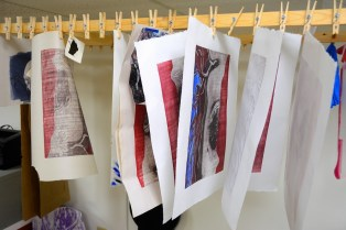 Prints hang on the rack at Paperworkers Local. (Karim Shamsi-Basha/Alabama NewsCenter)