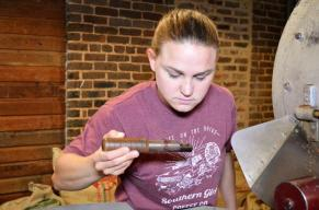 Leah Cleghorn of Southern Girl Coffee checks the roast on coffee beans. (Michael Tomberlin / Alabama NewsCenter)