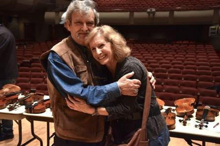 Marilyn Pipkin hugs Amnon Weinstein after giving him a violin repair kit. (Karim Shamsi-Basha/Alabama NewsCenter)
