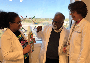 Gene Capture's chief technology officer, Dr. Krishnan Chittur, and vice president Paula Koelle explain the biochemical process to a student intern. (contributed)