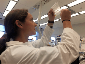 A GeneCapture scientist examines a prototype of the test cartridge that will screen for hundreds of pathogens in about 45 minutes. (contributed)