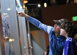 Mountain Brook's Jacob Ray points out details of a display at the Negro Southern League Museum to his son, 8-year-old Shep Ray. The pair made their first visit to the museum on Jackie Robinson Day. (Solomon Crenshaw Jr./Alabama NewsCenter)