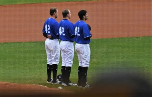 Barons starting pitcher Brian Clark, center, is flanked by third baseman Terry Michalczewski, left, and first baseman Nick Basto during the singing of the National Anthem. (Solomon Crenshaw Jr./Alabama NewsCenter)