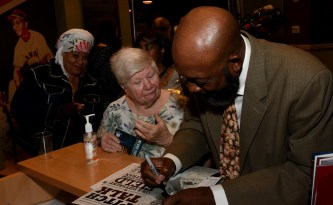 Football great Tony Nathan signs a poster during his visit to the Negro Southern League Museum last year. Nathan will appear with former high school rival and Alabama Crimson Tide teammate Jeff Rutledge at a Thursday benefit for Banks Academy. (Solomon Crenshaw Jr./Alabama NewsCenter)