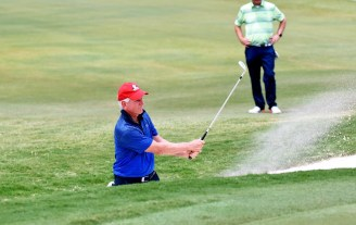 Tommy Tuberville blasts his way out of a sand trap on hole No. 18 at Greystone. (Solomon Crenshaw/Alabama NewsCenter)
