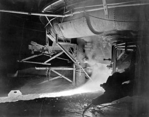 Molten iron flows from a furnace at the Sloss Furnaces complex in Birmingham. During the smelting process, iron ore, limestone and coke (processed coal) are blasted with superheated air, causing a series of chemical reactions to form molten slag (waste) and molten iron, which separates as it sinks to the bottom of the furnace. (From Encyclopedia of Alabama, courtesy of Birmingham Public Library Archives)