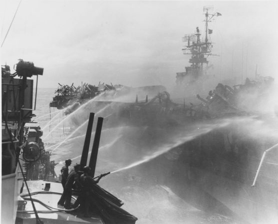Crewmen on USS Birmingham (CL-62) aim fire hoses on the burning USS Princeton (CVL-23), as their ship comes alongside to assist in damage-control measures, Oct. 24, 1944. (U.S. Naval Historical Center National Archives)