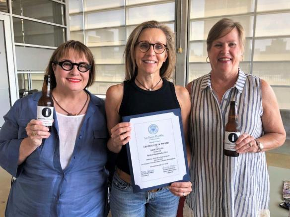 Becky Satterfield, left, and Rosemary Dallam, right, present Nancey Legg with better kambucha with the Les Dames d'Escoffier International Birmingham's New Entrepreneur Award. (contributed)