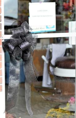 A black ribbon on the door at Vincent Oliver's Hippodrome Barber Shop in Woodlawn notifies visitors of Oliver's death. (Solomon Crenshaw Jr. / Alabama NewsCenter)