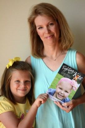 """Kate and Erin Miller with a copy of """"Fighting for Kate,"""" the story of Kate's successful battle with childhood leukemia. (Karim Shamsi-Basha/Alabama NewsCenter)"""