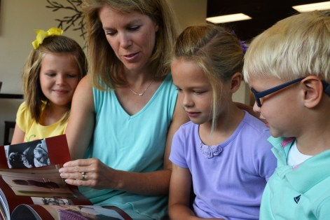 "Erin Miller and her children flip through a copy of ""Fighting for Kate."" (Karim Shamsi-Basha/Alabama NewsCenter)"