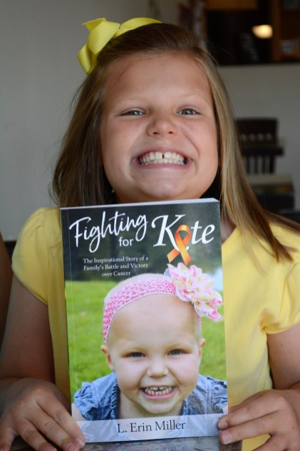 """Kate Miller, cancer-free for about five years, matches her grin on the cover of """"Fighting for Kate."""" (Karim Shamsi-Basha/Alabama NewsCenter)"""
