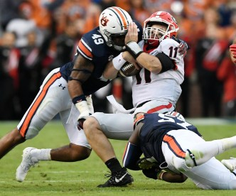 Auburn linebacker Deshaun Davis (57) and Auburn linebacker Darrell Williams (49) tackle Georgia's Jake Fromm in last year's regular-season victory over the Bulldogs. (Todd Van Emst/AU Athletics)