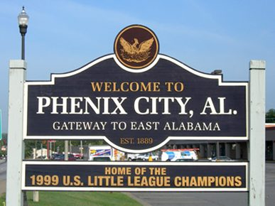 Phenix City is located on the Chattahoochee River on the Alabama-Georgia border, the county seat of Russell County. Its history is marked with crime and corruption, including the assassination of attorney general candidate Albert Patterson in 1954. The Phenix City sign includes a symbol of the phoenix, a mythological creature symbolizing resurrection that might be the origin of the city's name. (From Encyclopedia of Alabama, photograph by Jimmy Emerson)