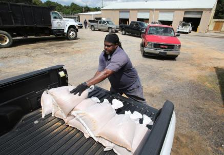 Saraland Public Works employee James Parker distributes free sandbags to residents in preparation of inland flooding associated with Tropical Storm Gordon on Tuesday in Saraland. (Mike Kittrell / Alabama NewsCenter)
