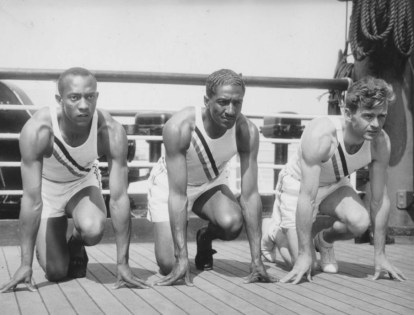 Photo of U.S. Olympic team sprinters (from left) Jesse Owens, Ralph Metcalfe and Frank Wykoff on the deck of the S.S. Manhattan before they sailed for Germany to compete in the 1936 Olympics. They're shown doing a light warm-up on the deck. (Associated Press, Wikipedia)