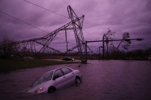 A vehicle sits partially submerged in floodwaters as a fallen electricity transmission tower lays on the ground in the background after Hurricane Michael hit in Panama City, Florida. (Luke Sharrett/Bloomberg)