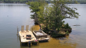 Workers prepare to shore up School Bus Island in June. The project was completed in time for boaters to enjoy the island on July 4. (contributed)