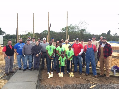Members of the Collins family stand with the Habitat for Humanity volunteers who are helping to build the family's home in Pleasant Grove. (contributed)