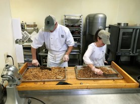 Stephen Reed, general manager of Iz Cafe, left, and Patti Montalbano Sansom, baker at Iz, prepare a batch of Iz Good Stuff Granola. (Michael Tomberlin / Alabama NewsCenter)