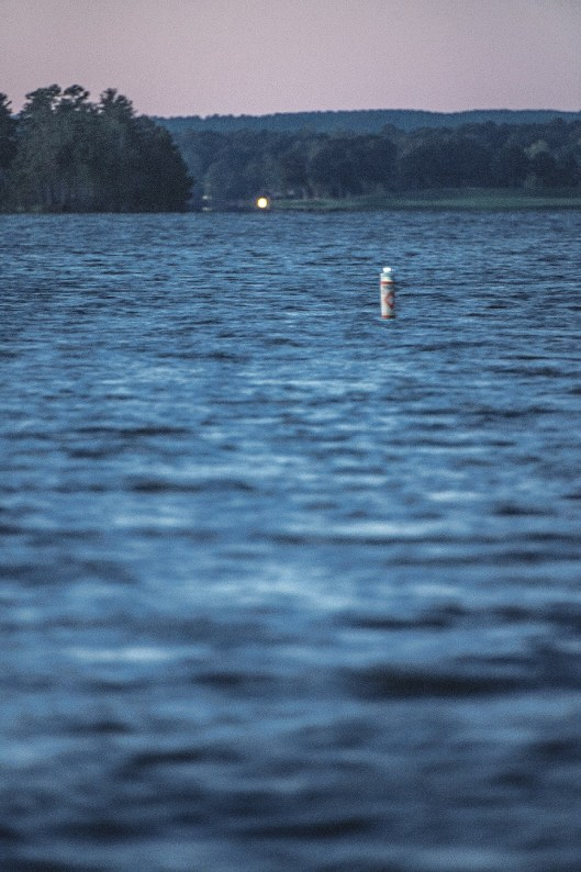 A lighted buoy shines across the water on Lake Martin. (Justin Averette/Shorelines)