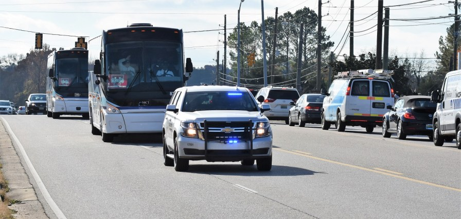 Buses carrying Thompson football players get a police escort. (Solomon Crenshaw Jr./Alabama NewsCenter)