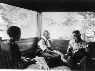 """Zora Neale Hurston interviews musicians Rochelle French and Gabriel Brown in this 1935 photo by musicologist Alan Lomax, taken in Eatonville, Florida. That same year, Hurston published her study of southern African-American folklore, """"Mules and Men."""" (From Encyclopedia of Alabama, courtesy of Library of Congress)"""