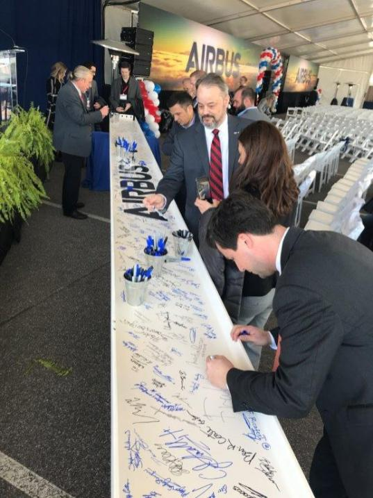Officials sign a beam that will be used in the construction of the new A220 assembly plant in Mobile. (Airbus)