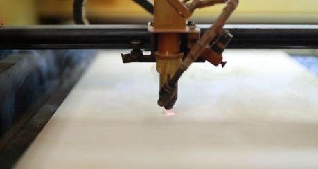 "The laser cutter goes to work on a custom ""Birmingham"" wood notebook. (Joe Allen)"