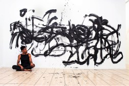 Jarrett Key sits in front of one of his hair paintings. (contributed)