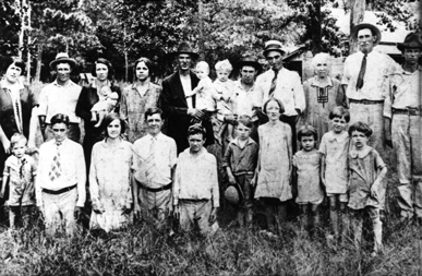 In a photograph taken at a family reunion, c. 1925, young Hiram (Hank) Williams stands, far left, in front of his mother, Lillie Williams. (From Encyclopedia of Alabama, courtesy of Hank Williams Boyhood Home/Museum)