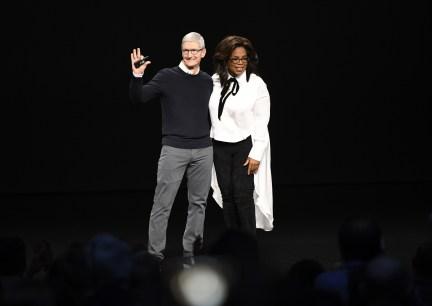 Tim Cook waves while onstage with Oprah Winfrey. (David Paul Morris/Bloomberg)