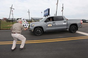 Talladega Superspeedway Chairman Grant Lynch waves the checkered flag as NASCAR driver Jeffrey Earnhardt leads fans into the new oversized tunnel. (contributed)