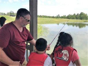 Justin Bailey, Maintenance team leader, shared his love of fishing with youngsters throughout the day. (Donna Cope/Alabama NewsCenter)