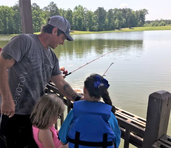 Gaston Mechanic Jason Leake helped children with their reels. (Donna Cope/Alabama NewsCenter)