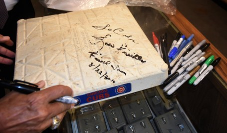 Lou Piniella signs a base from his last game for a Chicago Cubs fan. (Solomon Crenshaw Jr./Alabama NewsCenter)