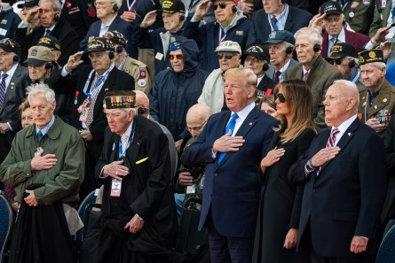 Donald Trump, third right, Melania Trump, second right, and William Matz, secretary of the American Battle Monuments Commission, right, sing the U.S. national anthem with World War II veterans during a ceremony at the Normandy American Cemetery and Memorial in Colleville-sur-Mer, France, on June 6, 2019. (Geert Vanden Wijngaert/Bloomberg)