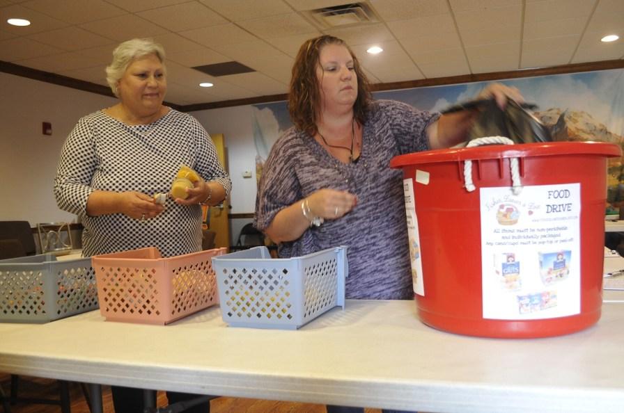 Fishes, Loaves and Love founder Lindsay Isbell, right, and Joanna Brady package food items at Cedar Grove Baptist Church. (Karim Shamsi-Basha/Alabama NewsCenter)
