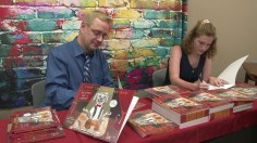 """Greg Kinnaird and Olivia Porrill sign copies of Kinnaird's new book, """"Tony the Theatre Dog, Puttin' on a Show"""" at the Gardendale Public Library. (Dennis Washington / Alabama NewsCenter)"""