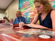 "Greg Kinnaird and Olivia Porrill sign copies of Kinnaird's new book, ""Tony the Theatre Dog, Puttin' on a Show"" at the Gardendale Public Library. (Dennis Washington / Alabama NewsCenter)"