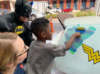 A patient at Children's of Alabama paints a race car from Talladega Superspeedway outside the hospital Friday morning. (Dennis Washington / Alabama NewsCenter)