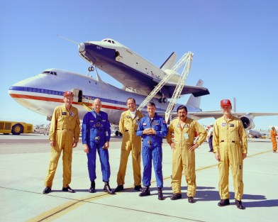 The flight crews of the space shuttle prototype Enterprise and NASA's modified Boeing 747 Shuttle Carrier Aircraft gathered in front of the piggyback pair following the final captive-carry flight in the shuttle Approach and Landing Tests on July 26, 1977. The SCA crew is in the yellow suits and the Enterprise crew wear the blue suits. (NASA)