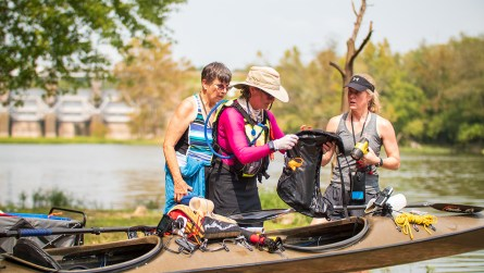 A team of racers prepares to get back in the water at the first portage on Weiss Lake. (Dennis Washington / Alabama NewsCenter)